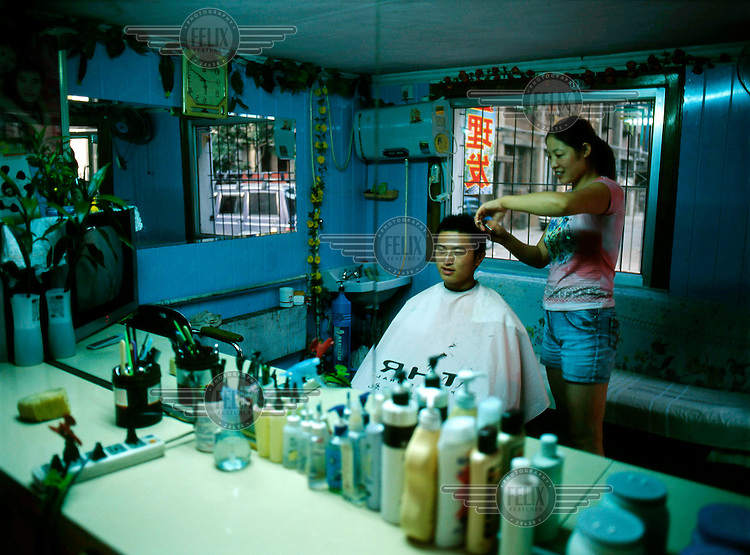 A man gets his hair cut by a hairdresser in a small, privately-run barbershop in eastern Beijing.