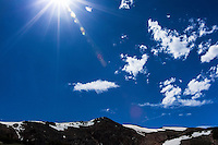 A sunburst against a blue sky with clouds and the rugged Rocky Mountains still streaked with patches of snow.