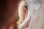 Young girl (8 years old) applying eye shadow make up to her face looking at herself in mirror Bothell Washington State USA MR