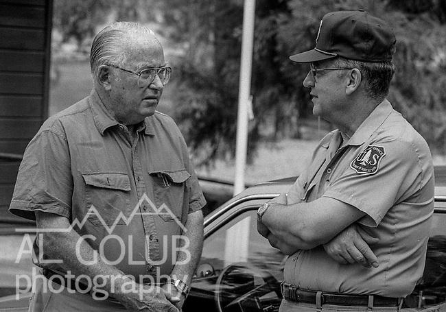 September 4, 1987 Greeley Hill, California --Stanislaus Complex Fire  -- Secretary of Agriculture Richard Lyng talks with Stanislaus National Forest Supervisor Blaine Cornell near Greeley Hill.  The Stanislaus Complex Fire consumed 28 structures and 145,980 acres.  One US Forest Service firefighter, David Ross Erickson, died from a tree-felling accident.