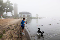 Kurt Miller and his dog Chloe play catch early in the  morning on the shore of Chautauqa Lake. Miller, now a  resident of the Washington DC area, has been coming to Chautuaqua since his childhood. Chautauqua Institution, NY. June 27, 2014. Photo by Brendan Bannon