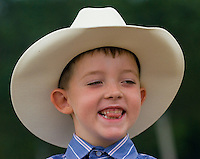A young boy wearing a white cowboy hat  smiles before entering the ring for a horse competition at the Knox County Fair in Mt. Vernon, Ohio.<br />