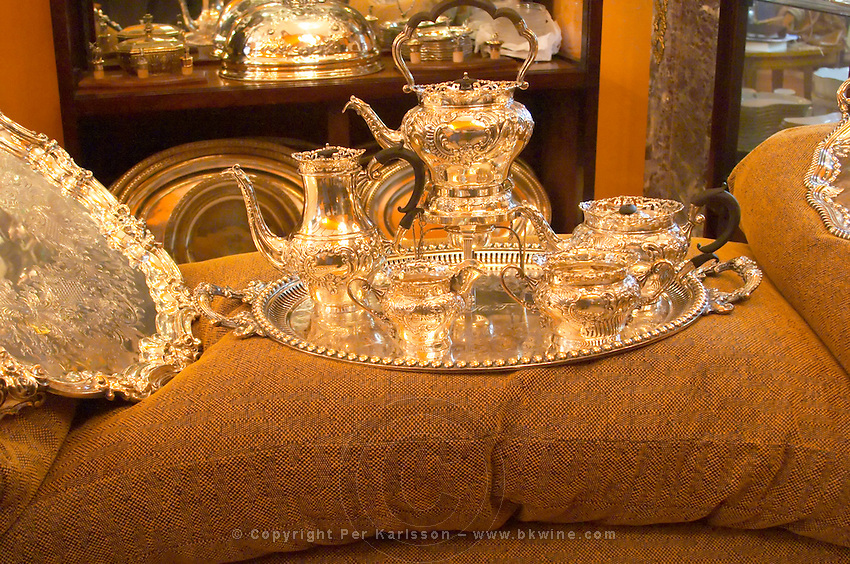 Interior of an antique shop in the San Telmo district around Plaza Dorrego Square, silver tea or coffee set with cream pot coffee pot handles in black ebony standing on a silver tray on a couch Calle Defensa Defence street Buenos Aires Argentina, South America