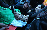 Relatives of the Palestinian Nidal Shatat, 29, who was shot dead by Israeli forces during clashes with Israeli troops in tents protest where Palestinians demand the right to return to their homeland at the Israel-Gaza border, mourn over his body during his funeral in the center of Gaza strip, on March 23, 2019. Photo by Ashraf Amra