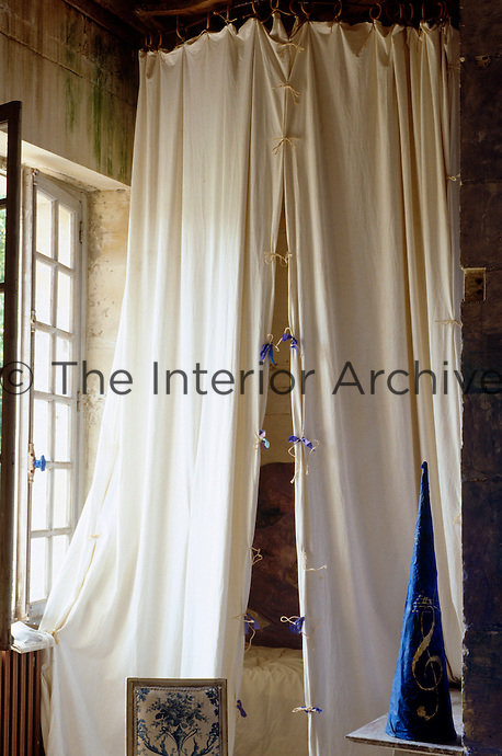 Lengths of natural linen tied together with string and ribbon conceal a small bed in this alcove