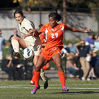 University of Miami forward Blake Stockton (29) works to disrupt passing Boston College forward Stephanie McCaffrey (9)..After two overtime periods, Boston College (gold) tied University of Miami (orange), 0-0, at Newton Campus Field, October 21, 2012.