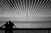 "UNITED STATES - FEBRUARY 8: Jenn Nadal and Derek Smith, from Ft. Lauderdale, Fl., ride the walkway in the National Gallery of Art through Leo Villareal's ""Multiverse,"" the artist's largest and most complex light sculpture. The work features approximately 41,000 computer-programmed LED that run through channels along the 200-foot-long space. (Photo by Chris Maddaloni/CQ Roll Call)"