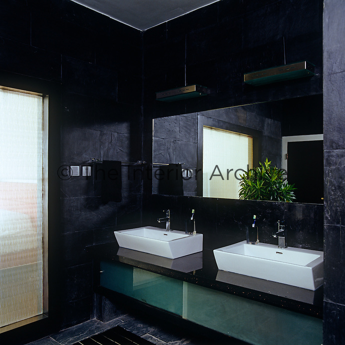 The walls of this contemporary bathroom are lined with black slate tiles