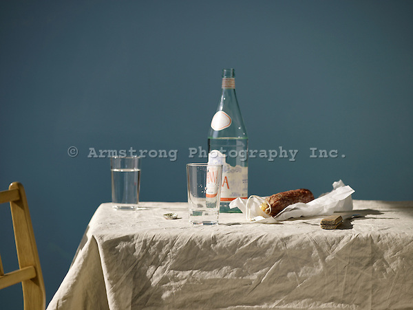 A casual table setting with a bottle of European spring water, empty glasses, and an artisan salami.