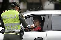CALI - COLOMBIA, 14-04-2020: Un oficial de la Policía requiere a un ciuadadano en Cali durante el día 22 de la cuarentena total en el territorio colombiano causada por la pandemia  del Coronavirus, COVID-19. / A Police officer requieres a citizen in Cali during the day 22 of total quarantine in Colombian territory caused by the Coronavirus pandemic, COVID-19. Photo: VizzorImage / Gabriel Aponte / Staff