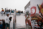 East Berlin, East Germany<br /> November 12, 1989<br /> <br /> Germans sit on top of the Berlin Wall at Potsdamer Platz to look at sections of the wall that were removed. Germans gathered as the wall is dismantled and the East German government lifted travel and emigration restrictions to the West on November 9, 1989.
