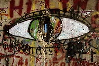 A painted eye forms part of the graffitti of the Berlin Wall with a glimpse through to the east side
