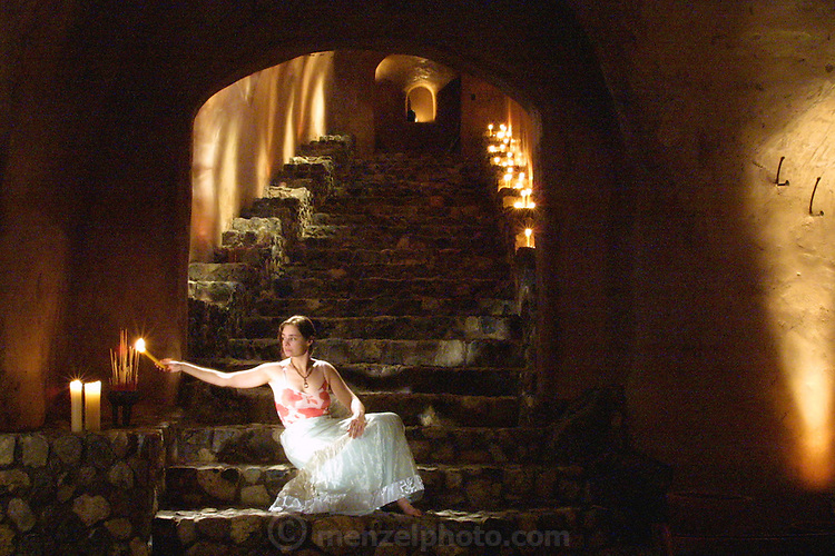Faith D'Aluisio lights incense underground in Menzel & D'Aluisio cave. Napa Valley, California, USA. ((PRIV)).