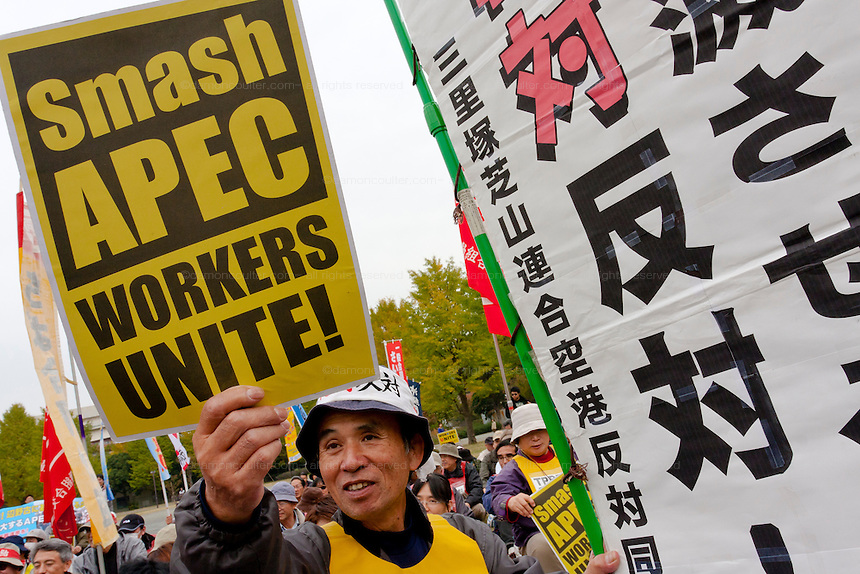 "A man holds a sign reading ""Smash Apec"" at an anti APEC (Asia Pacific Economic Conference)  Demo by left-wing activist groups and trade unions in Yokohama, Japan Sunday, November 14th 2010"