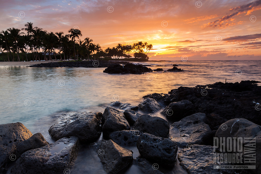 The sunset's colors are reflected in the waters at Pauoa Bay, Big Island.