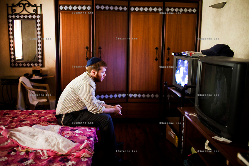 American Yeshiva Bentzion Plotkin watches old videos of The Rebbe as he takes a rest in his room in Mumbai, India. Yeshiva and Rabbi often reach out to secular and less religious Jews in India to help bring them closer to the religion and its rituals.