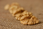 Walnut kernels closeup over sacking background with shallow artistic depth of field food still life