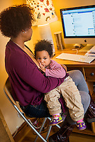 A mother  breastfeeds her 15 month old toddler whilst working at her computer at home.<br /> <br /> 18/10/12<br /> Harrow, England, UK