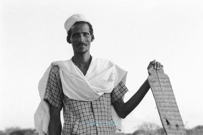 Somali man and prayer board in Wajir, a town on the  Kenya /Somalia  border populated mostly by Somalis.  Northern East Kenya.