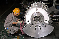 A Chinese technician examines a gear box at the Hudong Zhonghua Shipbuilding Co., LTD in Shanghai, China. China is the world's third largest shipbuilding nation after South Korea and Japan. While growing international interest in its lower building cost and domestic tanker demand to fulfill the country's hunger for energy is likely to push the country to the top position, the rapidly increasing price of steel has also undercut the industry's profitability..