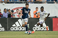 FOXBOROUGH, MA - JULY 27:  Carles Gil #22 passes the ball as Sebastian Mendez #8 approaches at Gillette Stadium on July 27, 2019 in Foxborough, Massachusetts.