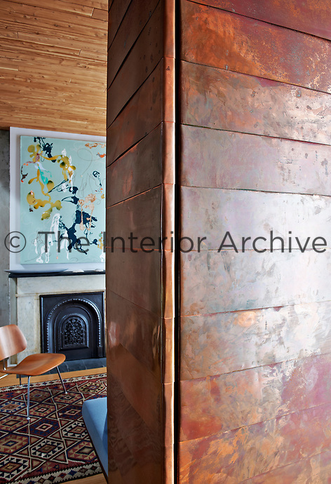 The walls and door in the entrance hall are lined with copper opening into a wood panelled sitting room