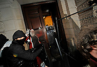 Police guard the entrance to the Treasury building during a student demonstration in Westminster, central London on the day the government passed a bill to increase university tuition fees.