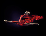 Surreal photograph of a woman with flowing red cloth that looks like a flame wrapping her nude body in a dynamic front split in mid-air isolated on black background