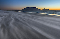 This 25 seconds long exposure appears remarkably calm, whereas in fact the wind was blowing with a gale-force, continuously blasting me and my camera with sand. This view of Cape Town City and its iconic Table Mountain was created at Sunset Beach, Table View.