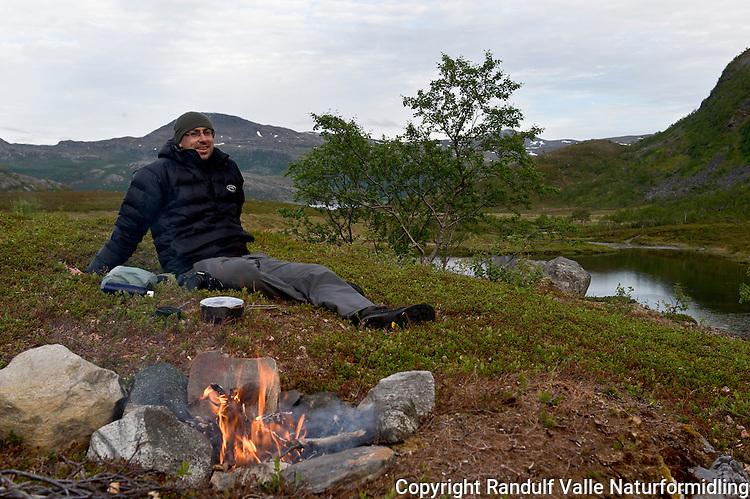 Mann slapper av ved bålet. ---- Man relaxing in front of camp fire.