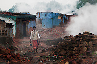 A man at the ruins of Laltenganj slum village. Most of the villagers are evacuated and settled in the newly build complex of Belgarhia. Few villagers are yet to be rehabilitated. A huge coal mine fire is engulfing the city of Jharia from all its sides. All scientific efforts have gone in vain to stop this raging fire. This fire is affecting lives of people living in and around Jharia. Jharkhand, India. Arindam Mukherjee