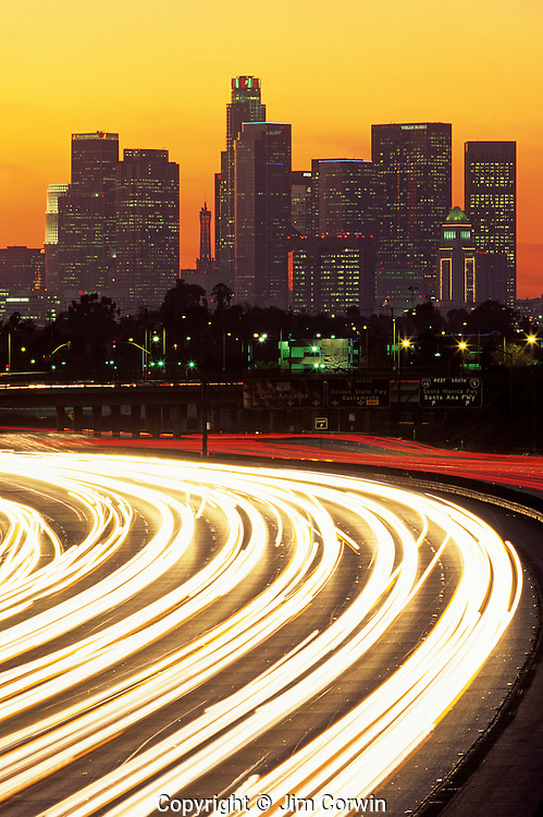 Sunset over LA Downtown District with skyscrapers with car light trails on Highway 10, Los Angeles, California USA
