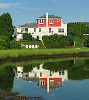 The facade of this New England summer house is perfectly reflected in the still water of the salt pond