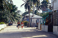 Young tourists carrying snorkeling gear along the main street on Caye Caulker, Belize