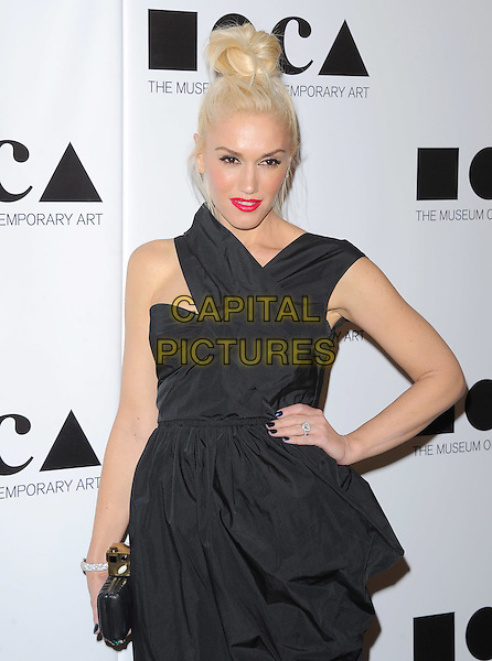 "Gwen Stefani  .at The 2011 MOCA Gala ""An Artist's Life Manifesto"" With Artistic Direction From Marina Abramovic held at MOCA Grand Avenue in Los Angeles, California, USA, November 12th 2011..half length ruched  black red lipstick hair up   clutch bag smiling                                                                              .CAP/RKE/DVS.©DVS/RockinExposures/Capital Pictures."