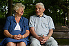 Older couple sitting on a park bench chatting,