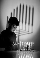 Boy lighting a Menorah at Chanuckah