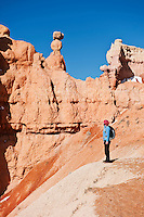Female hiker enjoys view from Queens Garden trail, Bryce Canyon national park, Utah, USA