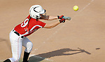 A female high school softball player attempts a bunt.
