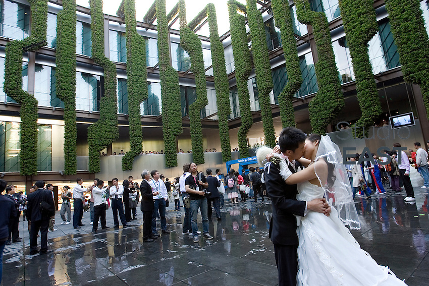 A newly married couple kisses in French Pavilion at Shanghai World Expo 2010, in Shanghai, China, on May 11, 2010. France Pavilion at Expo 2010 organized for the first time today French Romantic Weddings, allowing Chinese new couples to tie the knot in the beautiful French-style garden within the pavilion. Photo by Lucas Schifres/Pictobank