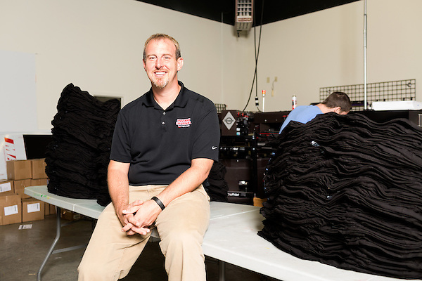 September 18, 2014. Raleigh, North Carolina.<br />  Chuck Sawyer's stores screen print 1000's of t-shirts a week when busy. Here he poses for a portrait in the production part of his main store.<br />  Chuck Sawyer, 37, is the owner of three Instant Imprints franchises, specializing in promotional materials such as t-shirts,signs and mugs. Sawyer wishes he had more saved for retirement and is encouraging his none employees to start thinking about how they will save for when they get older.<br /> Publication: AARP Bulletin<br /> Editor: Jenna Isaacson-Fuller<br /> Model Released<br /> Portrait