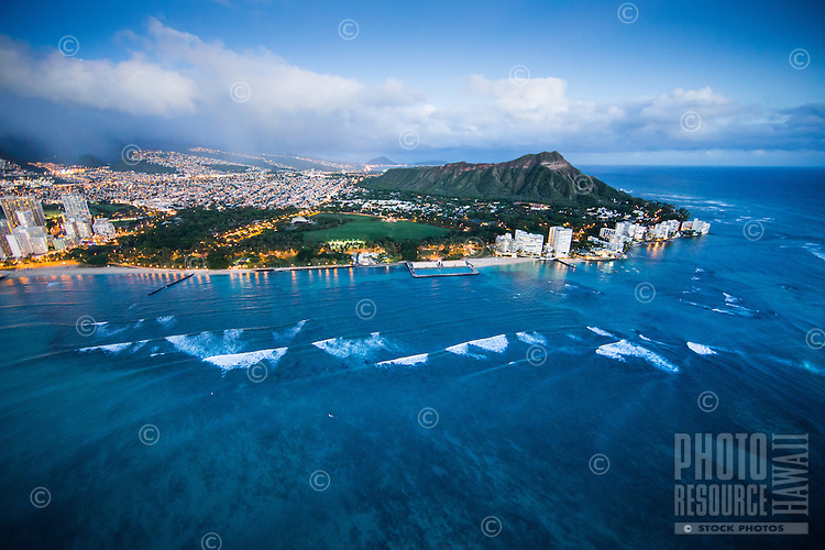 An aerial view of Waikiki, Kapi'olani Regional Park and Diamond Head Crater at dusk, Honolulu, O'ahu.