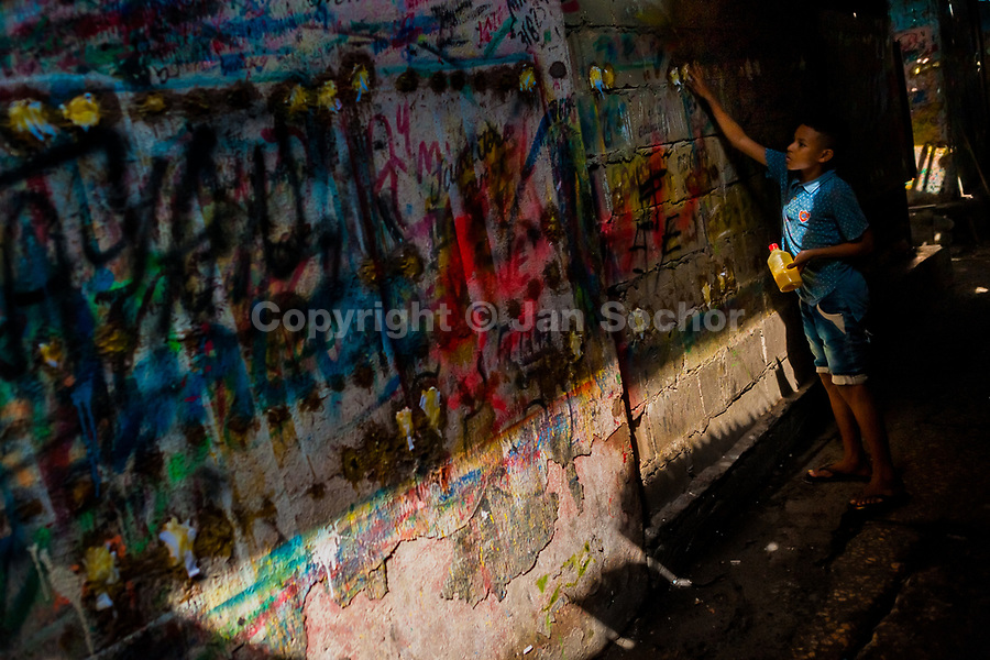 """A Colombian sign painter apprentice puts glue on the scribbled wall in the sign painting workshop in Cartagena, Colombia, 12 December 2017. Hidden in the dark, narrow alleys of Bazurto market, a group of dozen young men gathered around José Corredor (""""Runner""""), the master painter, produce every day hundreds of hand-painted posters. Although the vast majority of the production is designed for a cheap visual promotion of popular Champeta music parties, held every weekend around the city, Runner and his apprentices also create other graphic design artworks, based on brush lettering technique. Using simple brushes and bright paints, the artisanal workshop keeps the traditional sign painting art alive."""