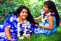 Young island girls in aloha style muumuus and leis sit outside on the grass.