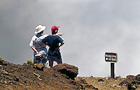 Two female tourists observing the clouds in the crater of HALEAKALA NATIONAL PARK on Maui in Hawaii USA