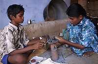 INDIA Tamil Nadu, Karur, child labour, boy and girl work in a polishing unit for artificial synthetic gems, they are putting the stones on bamboo sticks with wax before polishing / INDIEN, Kinderarbeit, Junge und Maedchen arbeiten in einer kleinen Edelsteinschleiferei im Dorf V. Pudur bei Karur, hier werden Halbedelsteine und kuenstliche Edelsteine poliert