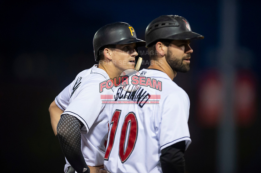 Indianapolis Indians center fielder Kevin Newman (2) talks to assistant head coach Jonathan Schwind (10) during an International League game against the Columbus Clippers on April 29, 2019 at Victory Field in Indianapolis, Indiana. Indianapolis defeated Columbus 5-3. (Zachary Lucy/Four Seam Images)