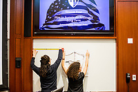 """Jesse Erin Posner (left), 31, and Arianna Grand, 27, put up Resistance School logo stencil on a whiteboard before a session of Resistance School  in the Starr Auditorium in the Belfer Building of Harvard University's John F. Kennedy School of Government, on Thurs., April 27, 2017. Posner works in Harvard's Department of Visual and Environmental Studies and serves as Production Designer for Resistance School. Grand is a Master in Public Policy grad student at Harvard's Kennedy School. Resistance School was started by progressive graduate students at Harvard after the Nov. 8, 2016, election of President Donald Trump. Resistance School describes itself as a """"practical training program that will sharpen the tools [needed] to fight back at the federal, state, and local levels."""" Resistance School puts on live lectures by leading progressives that are streamed and archived online alongside other information on the Resistance School website. During the lectures, teams of volunteers engage with followers on social media, including Facebook and twitter, sharing soundbytes, quotations, and supplementary materials as the lectures happen."""