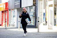 Pictured: A lady walks with her toilet paper in hand in Swansea City Centre during the Covid-19 Coronavirus pandemic in Wales, UK, Swansea, Wales, UK. Monday 23 March 2020