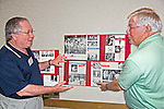 For 50th year reunion in Tulsa, OKlahoma, two senior men put up posters on wall of high school yearbook photographs and newspaper clippings